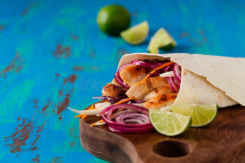 Tortilla wrap with grilled chicken and fresh vegetables. Flour tortilla wrap stuffed with grilled chicken fillet and fresh vegetables on blue wooden background royalty free stock images