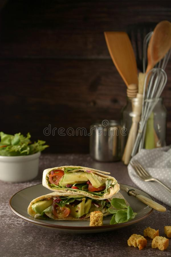 Tortilla wraps with avocado, cherry tomato. Healthy, vegan food. Take away snack royalty free stock images