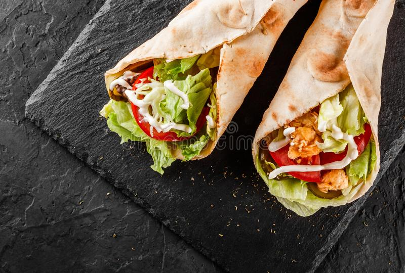 Tortilla wraps with grilled chicken, fresh vegetables and salad on black stone background. Healthy snack or take-away lunch. Top view, flat lay stock photography