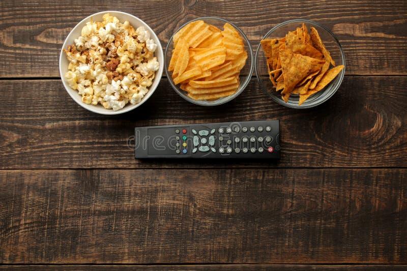 Tortillapopcorn, chiper och TV som är avlägsna på en brun träbakgrund begrepp av hållande ögonen på filmer hemma ovanför sikt royaltyfri foto