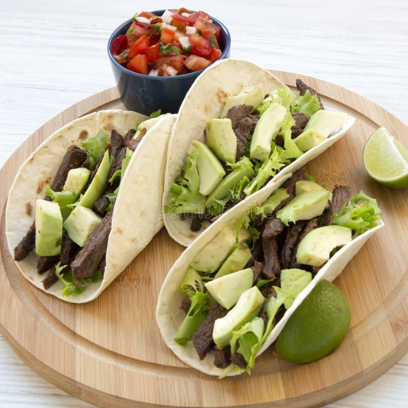 Tortillas καλαμποκιού με το ψημένους στη σχάρα βόειο κρέας, το αβοκάντο, τον ασβέστη και το salsa στο μπαμπού επιβιβάζονται, κινη στοκ φωτογραφίες με δικαίωμα ελεύθερης χρήσης