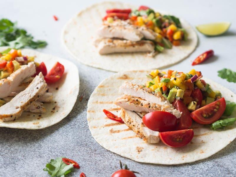Tortillas con el prendedero del pollo, la salsa del mango de la salsa y los tomates asados a la parrilla en fondo gris Concepto d fotografía de archivo