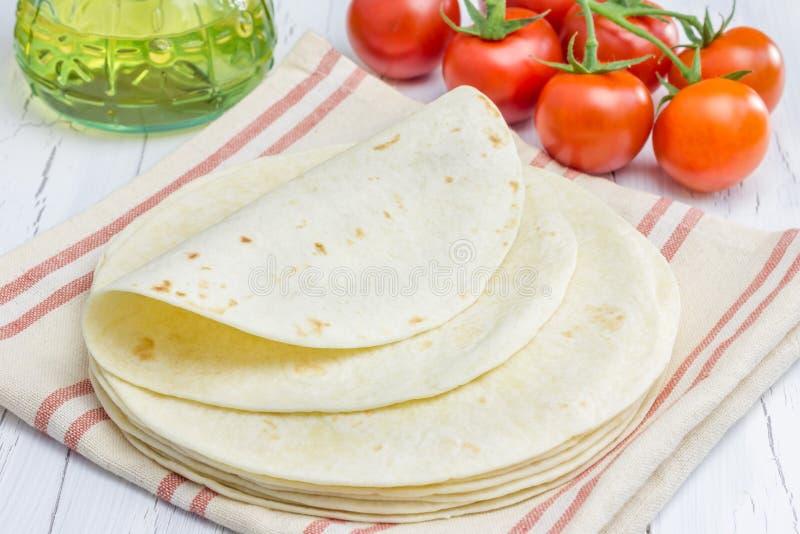 Tortillas de la harina del trigo integral con los tomates y el aceite de oliva en fondo imagen de archivo