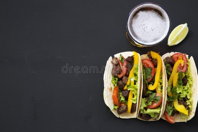 Tortillas de maïs avec du boeuf et légumes, bière et chaux sur un fond noir, vue supérieure Cuisine mexicaine photos stock