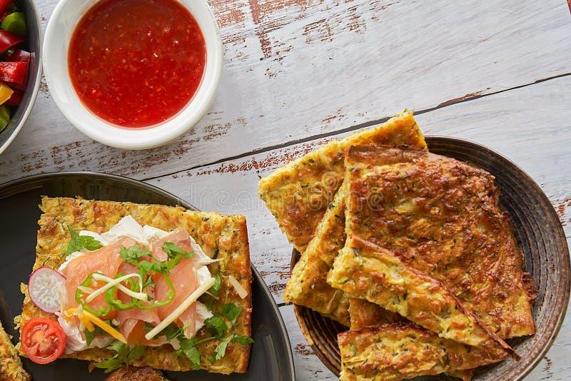 Tortillas del queso y del calabacín, salmón ahumado, raishes, tomates de cereza, crema del aguacate, queso cremoso, crema del tom fotografía de archivo