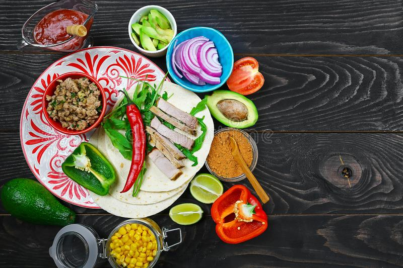 Tortillas flat and various vegetables for tacos or burrito making on rustic background, top view stock photos