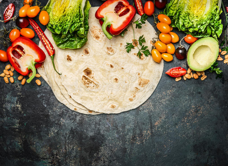 Tortillas flat and various vegetables for tacos or burrito making on rustic background, top view stock photography