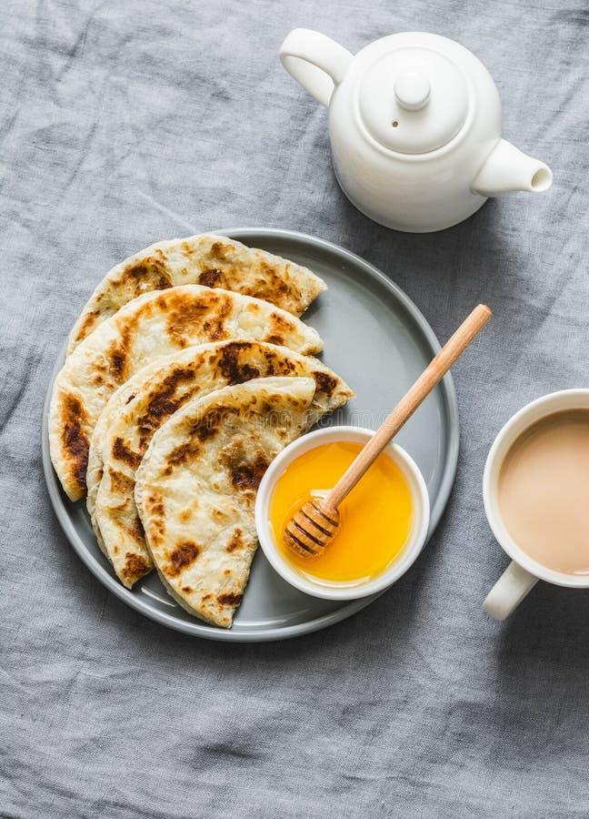 Tortillas indias del paratha con la miel y el té del masala en fondo gris, a fotografía de archivo libre de regalías