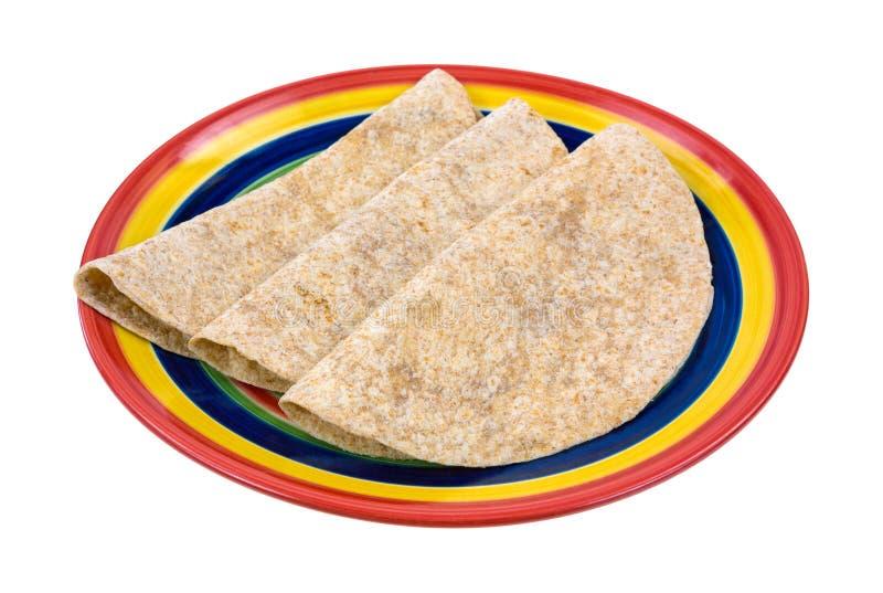 Tortillas inteiros do trigo dobrados na placa fotos de stock