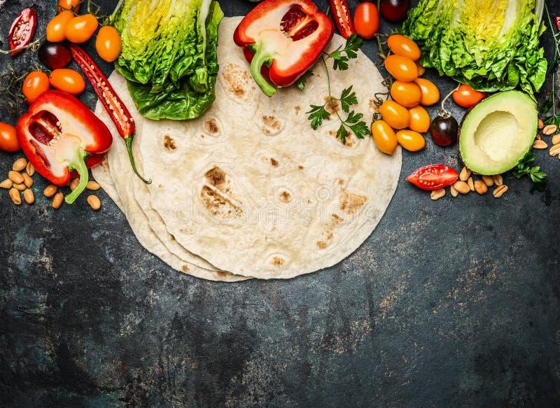 Tortillas plates et divers légumes pour les tacos ou le burrito faisant sur le fond rustique, vue supérieure photographie stock