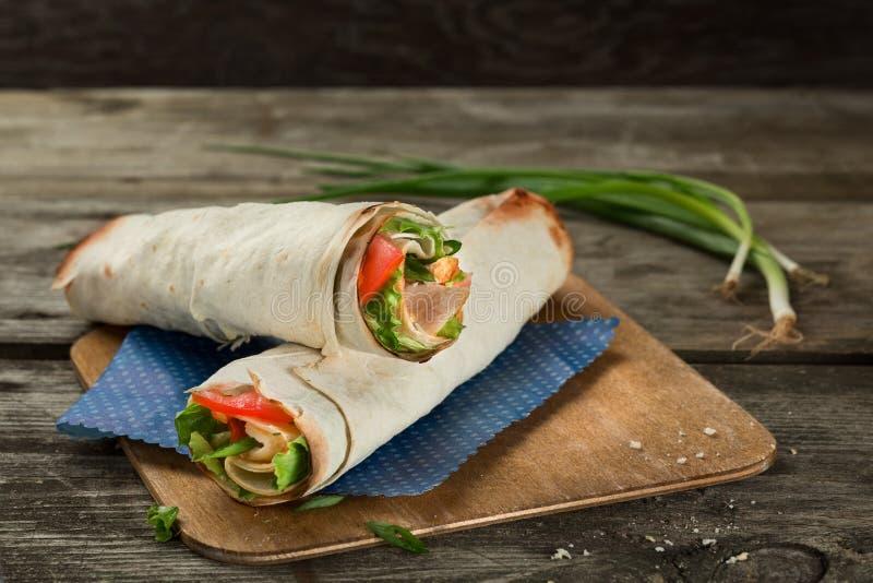 Tortillasjalen eller sjalsmörgåsen med skinka och grönsaker stänger sig upp Rullsmörgås med kött och grön sallad arkivbilder