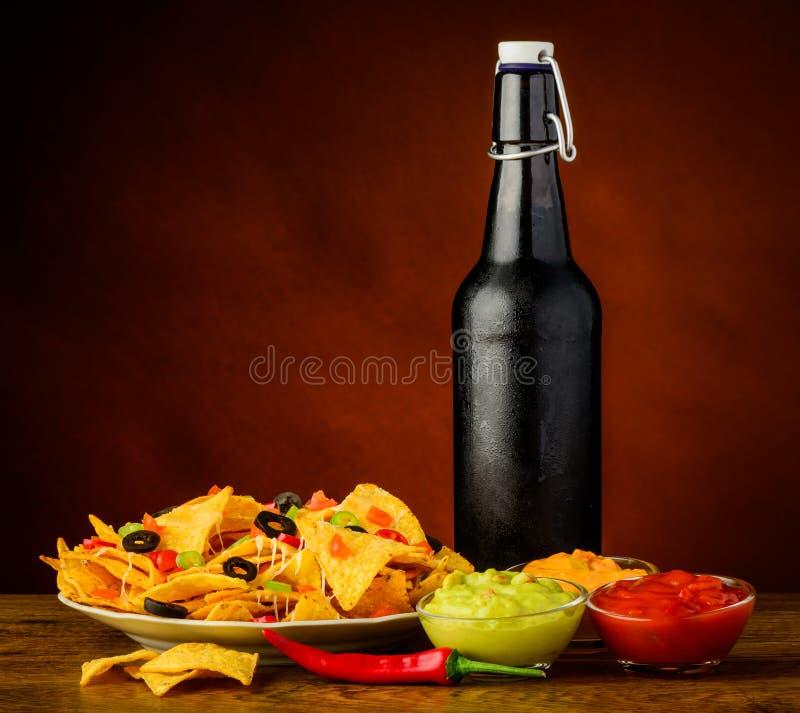 Tortillaspaanders, onderdompeling en bier stock afbeeldingen
