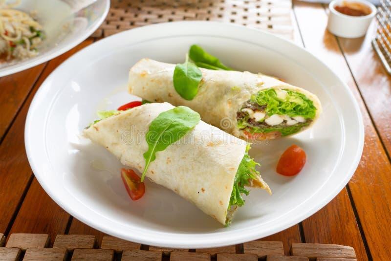 Tortillaverpackung mit Hühnerfleisch und -gemüse auf dem traditionellen Teller, der mit Spinat toping ist stockfoto