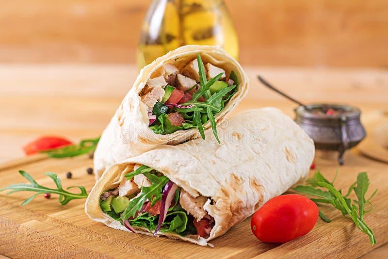 Tortillaverpackungen mit Huhn und Gemüse auf hölzernem Hintergrund Huhnburrito Gesunde Nahrung lizenzfreie stockfotos