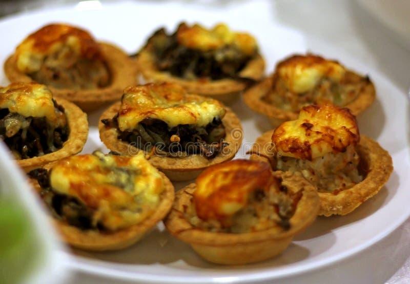 Tortini con formaggio ed i funghi su una tavola festiva fotografia stock