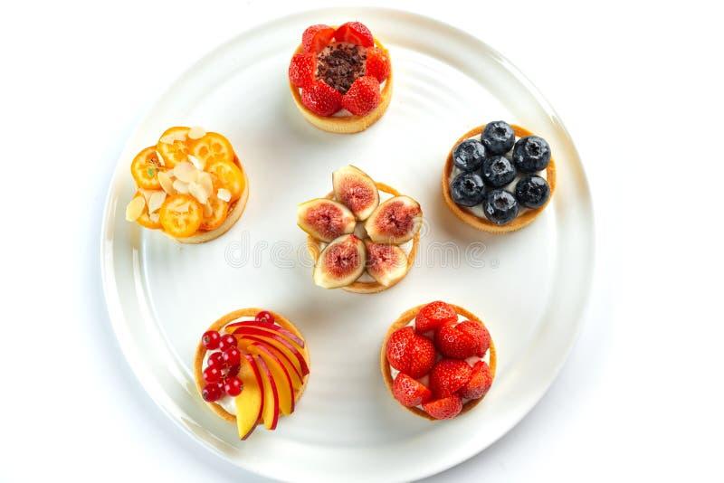 Tortini con i frutti e bacche in un piatto rotondo su un fondo bianco isolato immagini stock libere da diritti