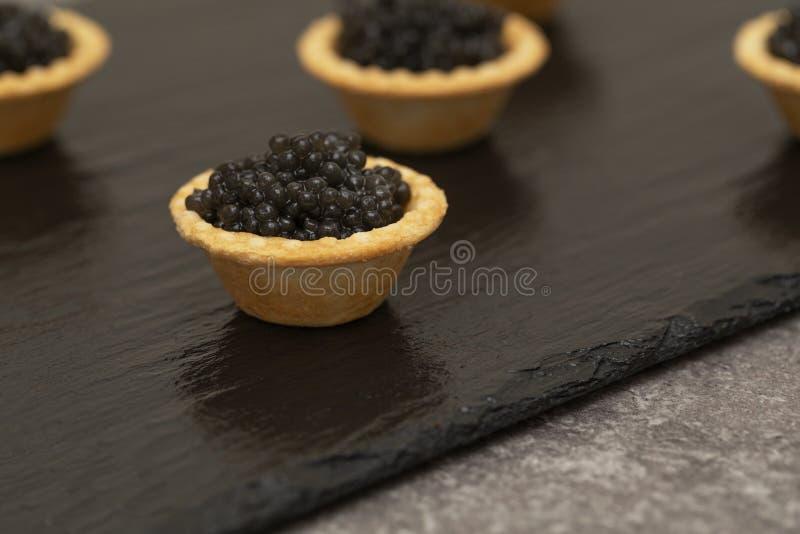Tortini con la fine nera del caviale su Fine dell'alimento gastronomico su, aperitivo delicatessen Alimento gastronomico Struttur fotografia stock