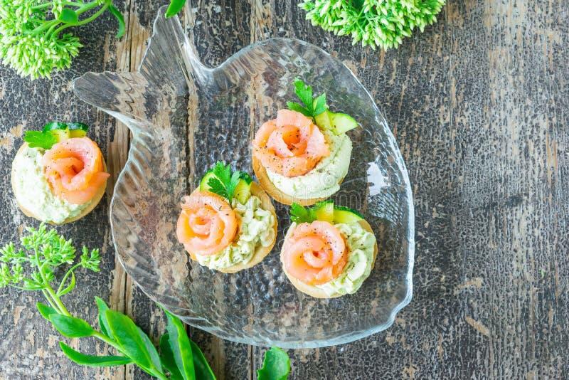 Tortini con la pasta dell'avocado, il salmone salato ed il prezzemolo immagine stock libera da diritti