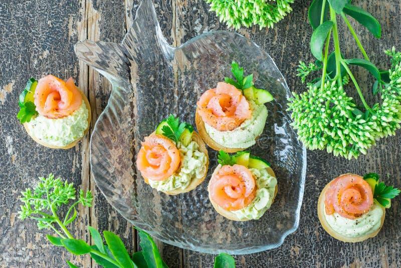 Tortini con la pasta dell'avocado, il salmone salato ed il prezzemolo fotografie stock libere da diritti