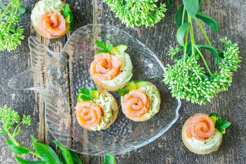 Tortini con la pasta dell'avocado, il salmone salato ed il prezzemolo fotografia stock