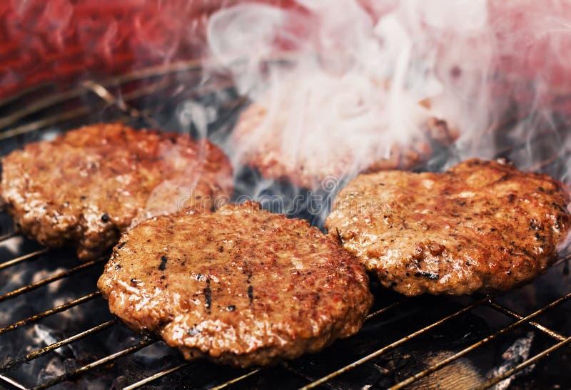 Tortini dell'hamburger su una griglia immagine stock libera da diritti