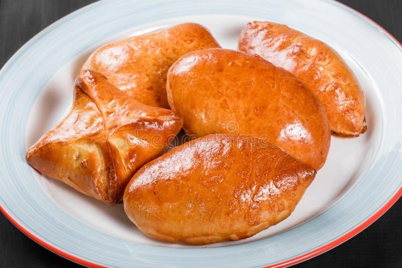 Tortini delle torte dei panini del pane fresco in piatto su fondo di legno nero Prodotti del forno Prima colazione calda e sana fotografie stock libere da diritti