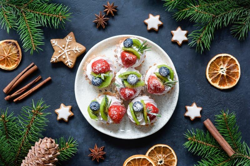 Tortini o bigné delle canape di Natale con crema e le bacche sul piatto bianco Alimento di vacanze invernali fotografia stock