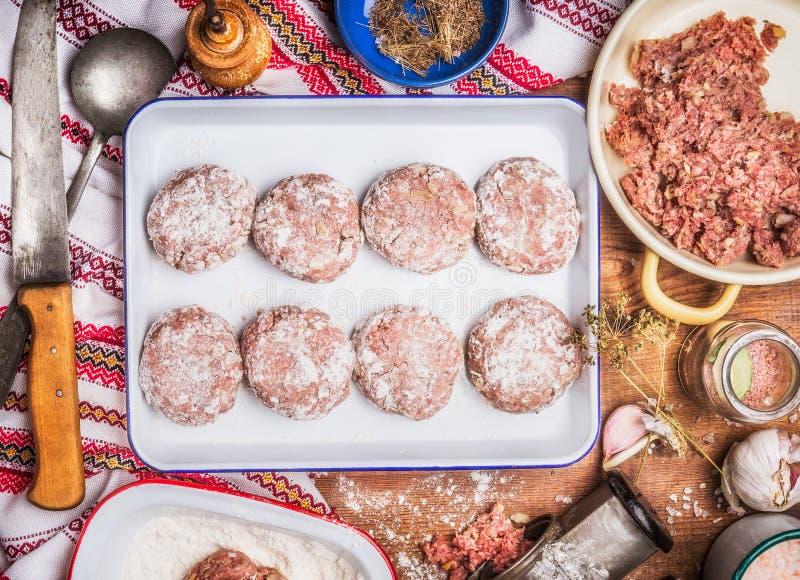 Tortini saporiti della carne che cucinano preparazione in ciotola smaltata con il coltello da cucina e gli ingredienti su fondo r immagini stock libere da diritti