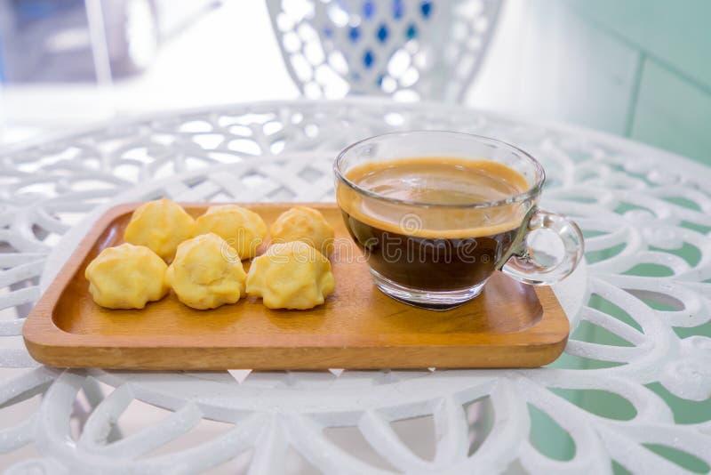 Tortowy eclair, Kremowi chuchy lub Profiterole z filiżanką w drewno talerzu na białym stole obrazy royalty free