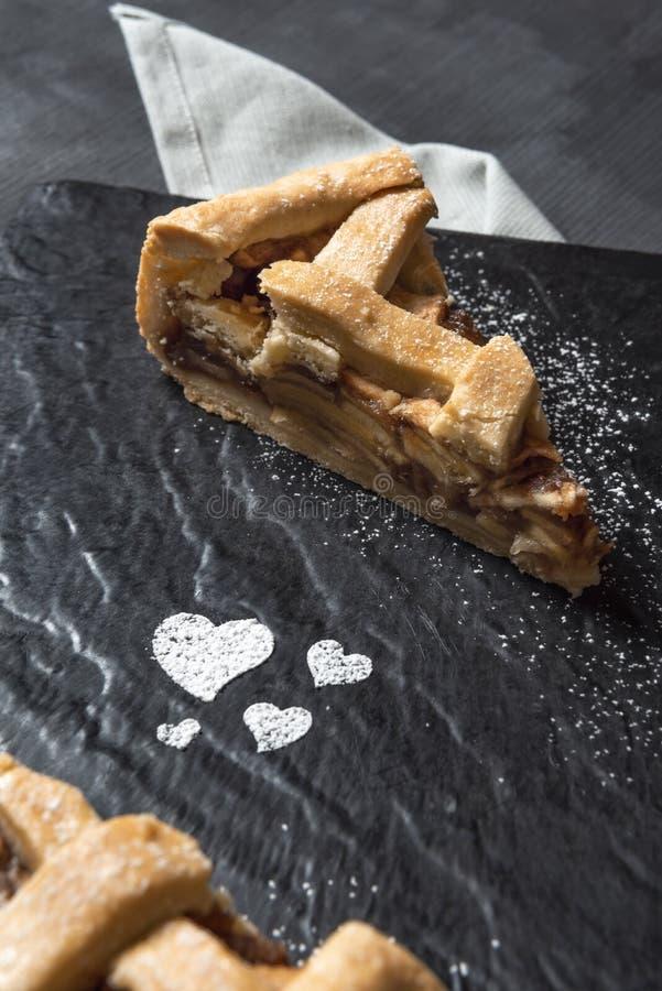 Tortowy plasterek i sproszkowani cukrowi serca jabłkowe ciasto domowej roboty zdjęcia royalty free