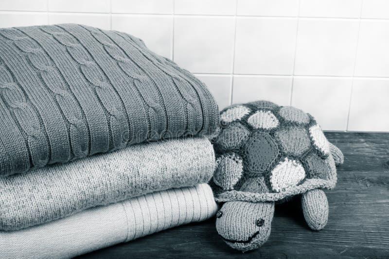 Tortue tricotée de jouet avec la pile de vêtements tricotés sur t en bois photos stock