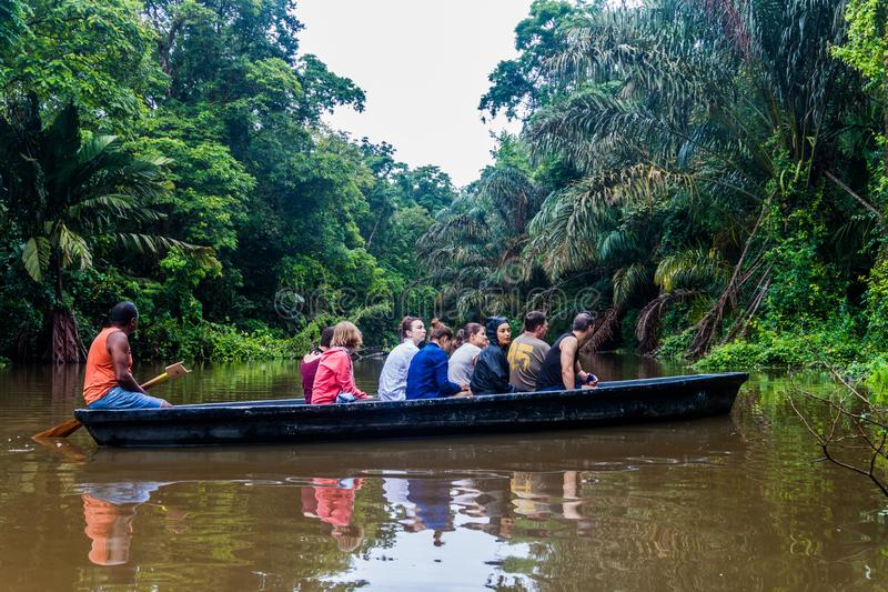 TORTUGUERO, COSTA RICA - MAY 15, 2016: Boat with tourists during wildlife watching tou royalty free stock images