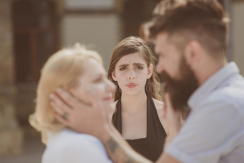 Tortures of jealousy. Bearded man cheating his woman with another girlfriend. Jealous girl look at couple in love on. Tortures of jealousy. Bearded men cheating stock image