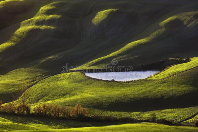 Toscana, paisaje rural en la puesta del sol, Italia Lago y campos verdes foto de archivo libre de regalías