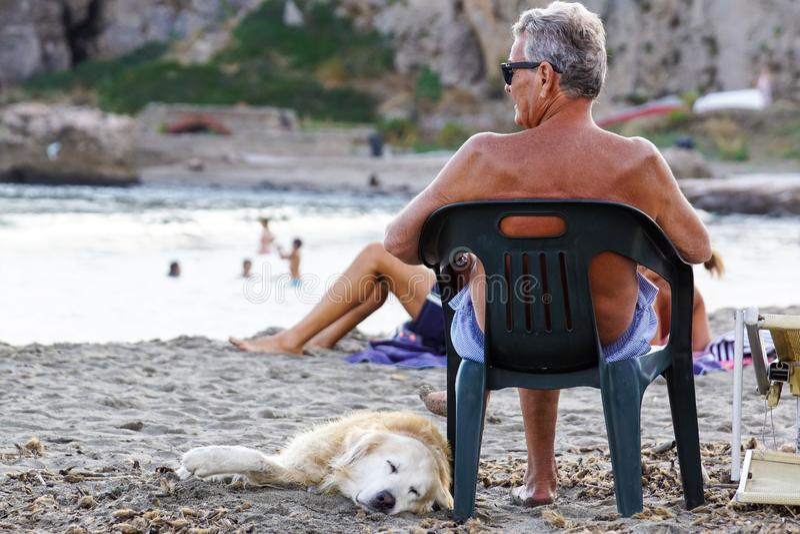 TOSCANIË, ITALIË 17 JULI 2018: Rijpe mens die op een ligstoel rusten die aan muziek luisteren die zijn hond op het strand petting stock foto's