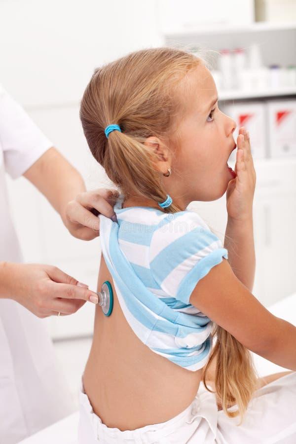 Toser a la niña en el doctor fotografía de archivo