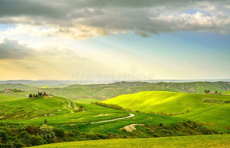 Toskana, ländliche Sonnenunterganglandschaft. Landschaftsbauernhof, weiße Straße und Zypressenbäume. stockbild
