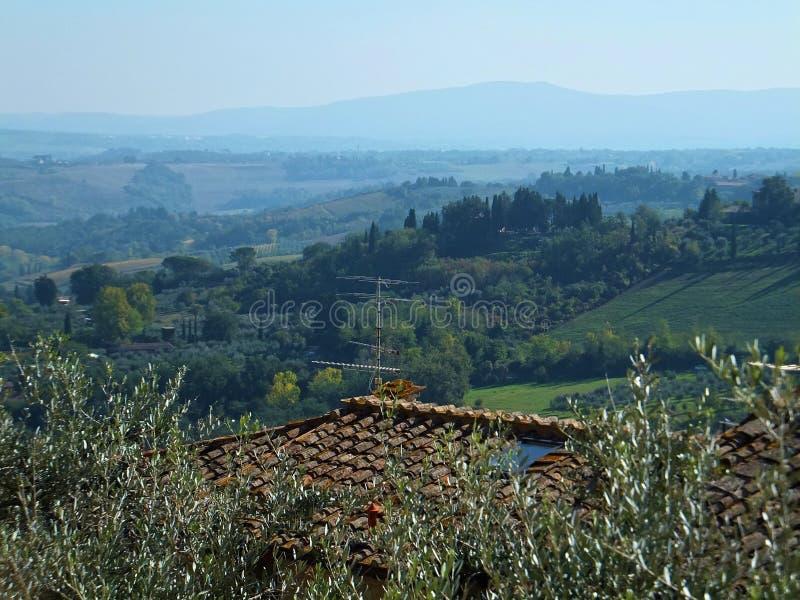 Toskanka krajobraz, zieleni drzewa i pola ustępuje, błękitne góry i wzgórza Czerwony gontu dach w przedpolu zdjęcia royalty free
