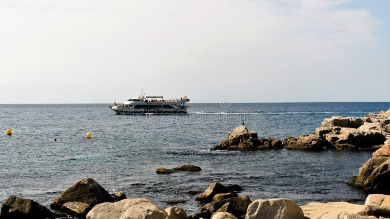 Tossa de Повреждать, Испания, август 2018 Прогулочное судно, проходя пляжем стоковые изображения rf