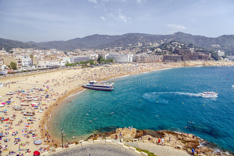 Tossa de Mar Beaches, Spain. TOSSA DE MAR, SPAIN - JUNE 08, 2014: A crowd of vacationers enjoy the warm beaches of Costa Brava. Former fishing village is now a stock images