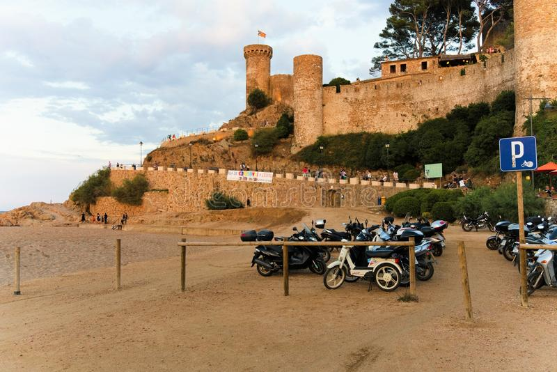 Tossa de Mar, Catalonia, Espanha, em agosto de 2018 Vista da fortaleza e estacionamento das motocicletas no por do sol foto de stock