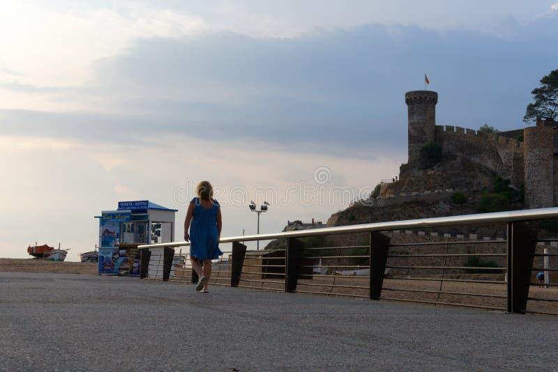 Tossa de Mar, Cataluña, España, agosto de 2018 Fortaleza, puente viejo y muchacha caminando a la playa imagen de archivo