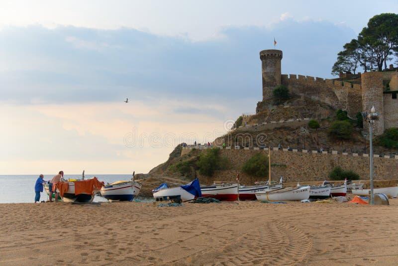 Tossa de Mar, Espanha, em agosto de 2018 Opinião a fortaleza, barcos na praia e pescadores fotos de stock