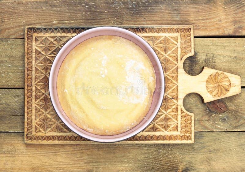 Tosse em uma tigela cor-de-rosa numa prancha de corte de madeira feita à mão foto de stock