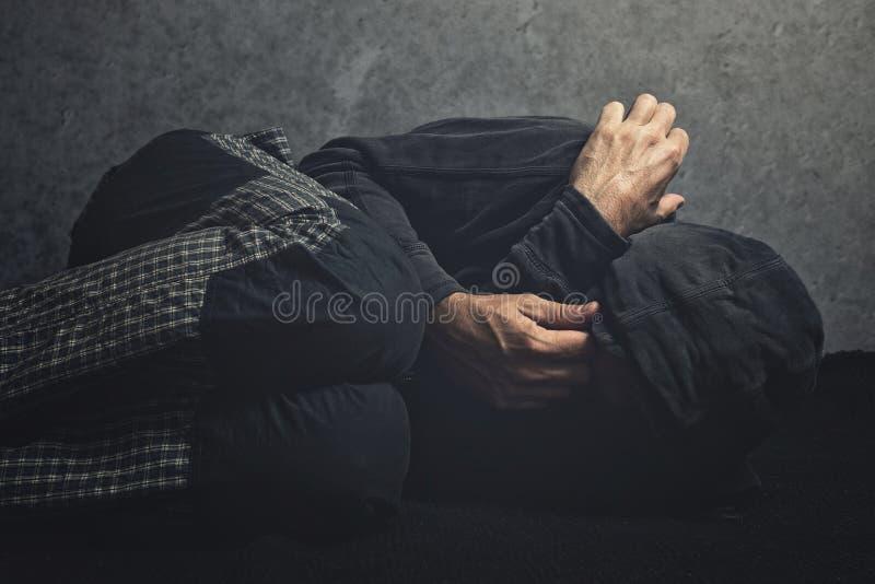 Tossicomane che mette sul pavimento nell'agonia fotografia stock