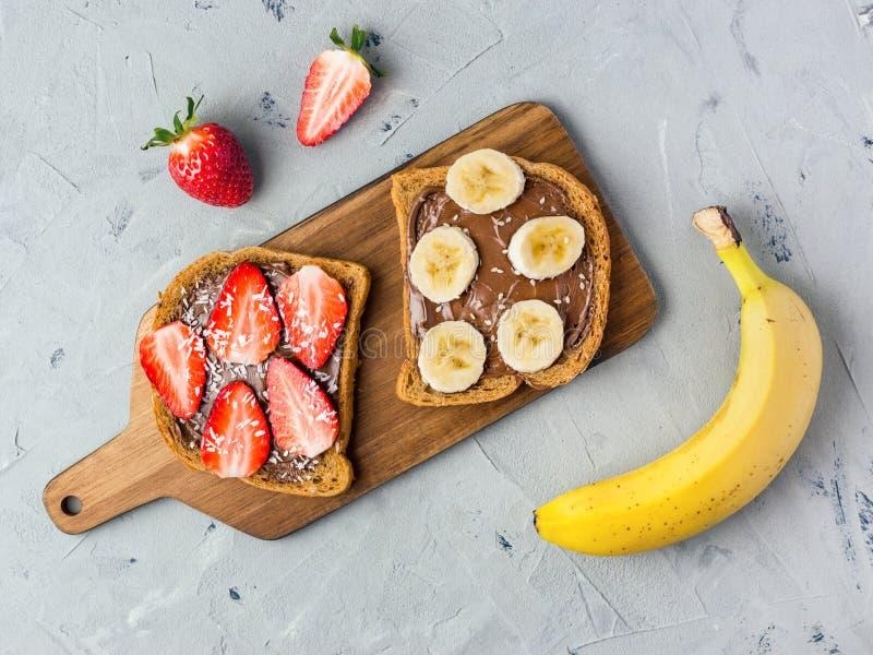 Tostada con el chocolate y las frutas en un tablero de madera Fresas y pl?tanos en el fondo de piedra de la tabla de cocina Visi? foto de archivo
