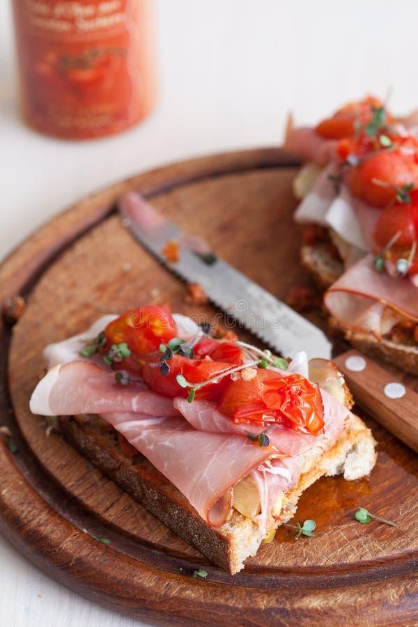 Tostada con el jamón y los tomates imagenes de archivo