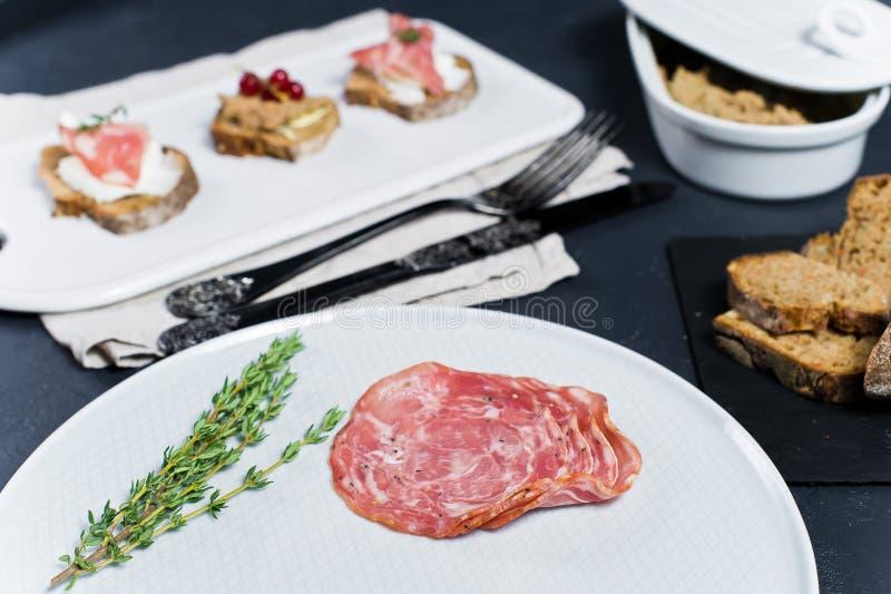Tostada con la coronilla de Parma, del salami y del ganso en una tajadera blanca imagen de archivo
