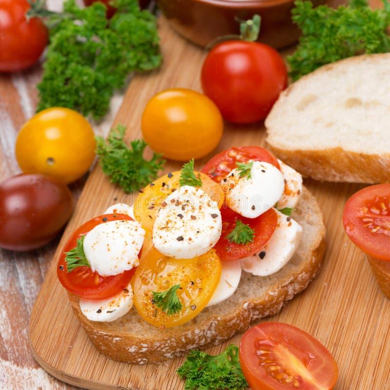 Tostada con la mozzarella y los tomates de cereza coloridos fotografía de archivo