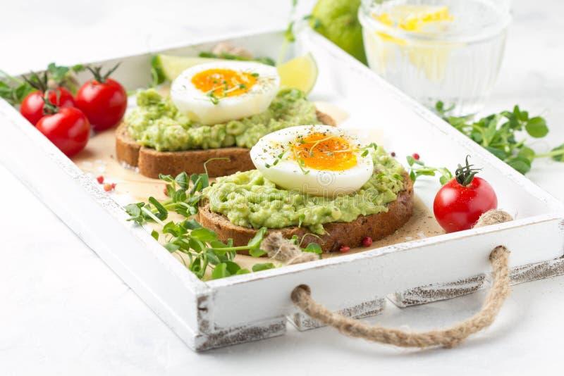 Tostada con pur? del aguacate y el huevo pasado por agua en la bandeja blanca, yema de huevo l?quida, desayuno delicioso, bocadil fotos de archivo libres de regalías